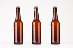 Tres botellas de cerveza marrones del longneck imitan para arriba Fotografía de archivo libre de regalías