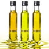 Tres botellas de diverso aceite de oliva en reflexiones líquidas Imágenes de archivo libres de regalías