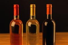 Tres botellas de vino en la tabla de madera y el fondo negro Imagenes de archivo
