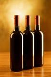 Tres botellas de vino rojo en la tabla de madera y el fondo de oro Foto de archivo libre de regalías