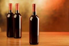 Tres botellas de vino rojo en la tabla de madera y el fondo de oro Foto de archivo