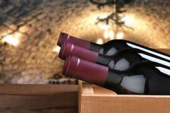 Tres botellas de vino tinto en un cajón de madera en una bodega foto de archivo