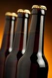 Tres botellas marrones de cerveza que se colocan en fila en fondo anaranjado Fotografía de archivo libre de regalías