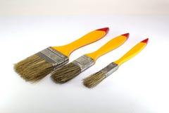 Tres brochas con una anchura de 1 pulgada, 2 pulgadas y 0 5 pulgadas con las manijas amarillas en un fondo blanco foto de archivo libre de regalías