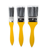Tres brochas de diversos tamaños con la manija amarilla Imágenes de archivo libres de regalías