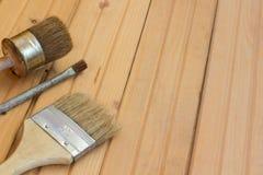 Tres brochas en un piso de madera Foto de archivo libre de regalías