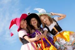 Tres brujas lindas con los pulgares para arriba Foto de archivo
