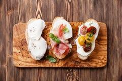 Tres bruschettas con la mozzarella, el jamón y los tomates Fotos de archivo libres de regalías