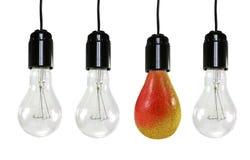 Tres bulbos eléctricos y una pera Imagen de archivo