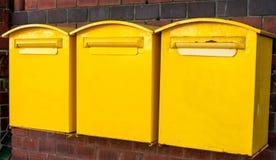 Tres buzones amarillos Imagen de archivo libre de regalías