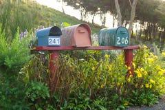 Tres buzones de correos en un banco rojo de forma de Nueva Zelanda imagen de archivo