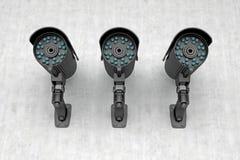 Tres cámaras de vigilancia en la pared Imágenes de archivo libres de regalías