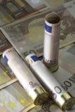 Tres 12 cáscaras de escopeta del calibre cargaron con cincuenta cuentas euro En fondo euro de cincuenta billetes de banco Fotos de archivo