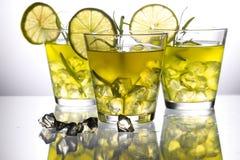 Tres cócteles amarillos con el limón y el romero que se colocan sobre el vidrio en estudio Fotos de archivo libres de regalías