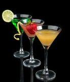 Tres cócteles cosmopolitas rojos de los cócteles adornados con la fruta cítrica Imagenes de archivo