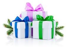 Tres cajas atadas con las cintas coloreadas arquean y la rama de árbol de pino aislada fotografía de archivo libre de regalías