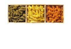 Tres cajas de madera con fusilli coloreado están en un fondo blanco imagenes de archivo