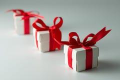 Tres cajas de regalo blancas con la cinta roja en fila Foto de archivo libre de regalías
