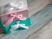 Tres cajas de regalo, blancos, rosas y turquesas Fondo de madera Imagen de archivo