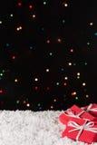 Tres cajas de regalo en la nieve con las luces de la Navidad en el fondo Fotos de archivo libres de regalías