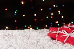 Tres cajas de regalo en la nieve con las luces de la Navidad en el fondo Imagen de archivo libre de regalías