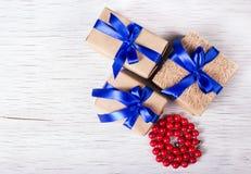 Tres cajas de regalo hechas del papel de Kraft con las cintas azules y las gotas del coral rojo Rectángulos de regalo en un fondo Imagen de archivo