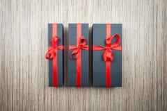Tres cajas de regalo negras con un arco en una tabla de madera imagen de archivo