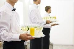 Tres camareros en las corbatas de lazo que sostienen las bandejas Imagen de archivo libre de regalías