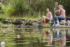 Tres caminantes que se sientan por el lago Fotos de archivo libres de regalías