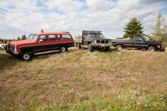 Tres camiones del trabajo en un campo fotografía de archivo