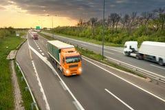 Tres camiones en la carretera en la puesta del sol en el movimiento Imagen de archivo libre de regalías