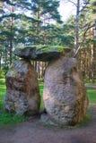 Tres cantos rodados de piedra enormes se apilan en una figura en un coniferou Imagenes de archivo