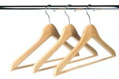 Tres capas/suspensiones de ropa de madera en un carril de la ropa Fotografía de archivo