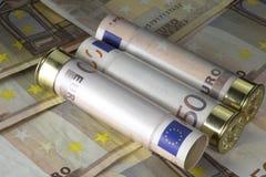 Tres 12 cartuchos de la escopeta del calibre cargaron con cincuenta cuentas euro En fondo euro de los billetes de banco Imágenes de archivo libres de regalías