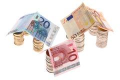 Tres casas hechas de monedas euro y de billetes Fotografía de archivo libre de regalías