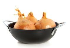 Tres cebollas comestibles en un wok negro Foto de archivo