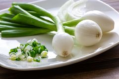 Tres cebollas mexicanas grandes que son las cebollas verdes que se han permitido crecer más grandes en una placa blanca con un ci imagenes de archivo