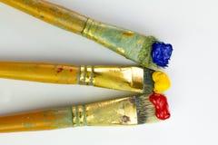Tres cepillos con la pintura roja, amarilla y azul en el fondo blanco Lugar para el texto, para la bandera, para el sitio Imagen de archivo libre de regalías
