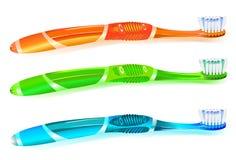 Tres cepillos de dientes coloridos Imagenes de archivo