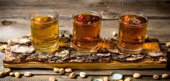 Tres cervezas en soporte del abedul con los pistachos alrededor Fotos de archivo libres de regalías