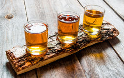 Tres cervezas en soporte del abedul En un vector de madera Fotos de archivo