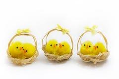 Tres cestas de polluelos de pascua sobre blanco Foto de archivo