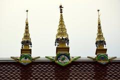 Tres chapiteles de oro en un tejado del templo en Tailandia Fotos de archivo libres de regalías