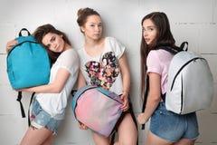 Tres chicas jóvenes con las mochilas Imagen de archivo libre de regalías
