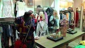 Tres chicas jóvenes divertidas eligen la ropa en la tienda almacen de video