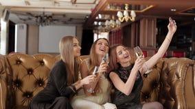 Tres chicas jóvenes están haciendo la foto del selfie en un restaurante almacen de metraje de vídeo