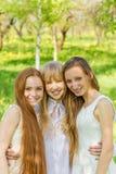 Tres chicas jóvenes hermosas en los vestidos blancos en verano Imagen de archivo libre de regalías
