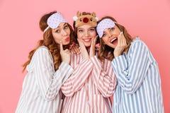 Tres chicas jóvenes hermosas 20s que llevan pijamas rayados coloridos Foto de archivo libre de regalías