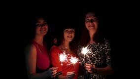 Tres chicas jóvenes que celebran con una bengala almacen de video