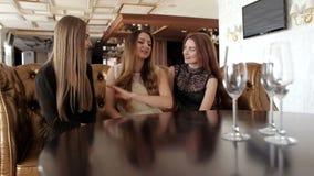 Tres chicas jóvenes que hablan animatedly sentarse en una tabla en el restaurante almacen de video